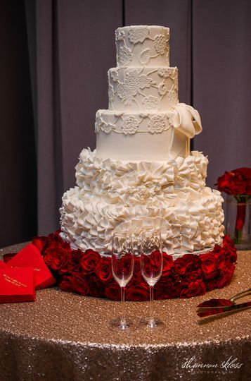 White wedding cake with red roses at the bottom