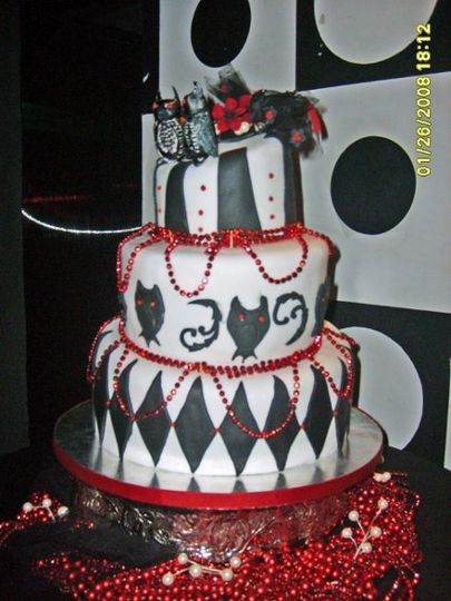Styled in the Goth style, this cake features two owls, in love with each other atop the harlequin...