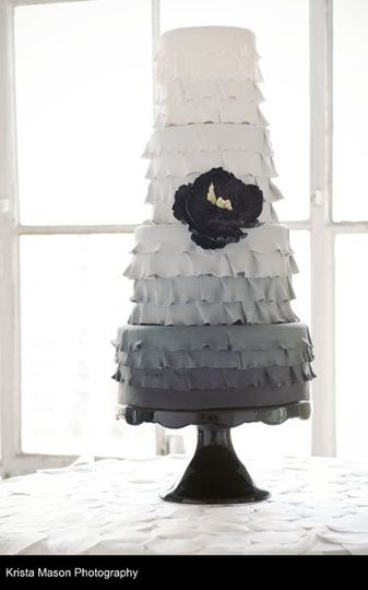 Four tier cake with ruffles featuring a sugar peony.