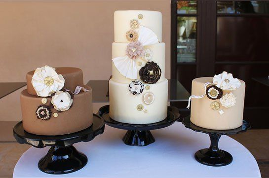 """A trio of cakes featuring chocolate, white chocolate and mocha fondant, sugar """"fabric"""" flowers, and..."""