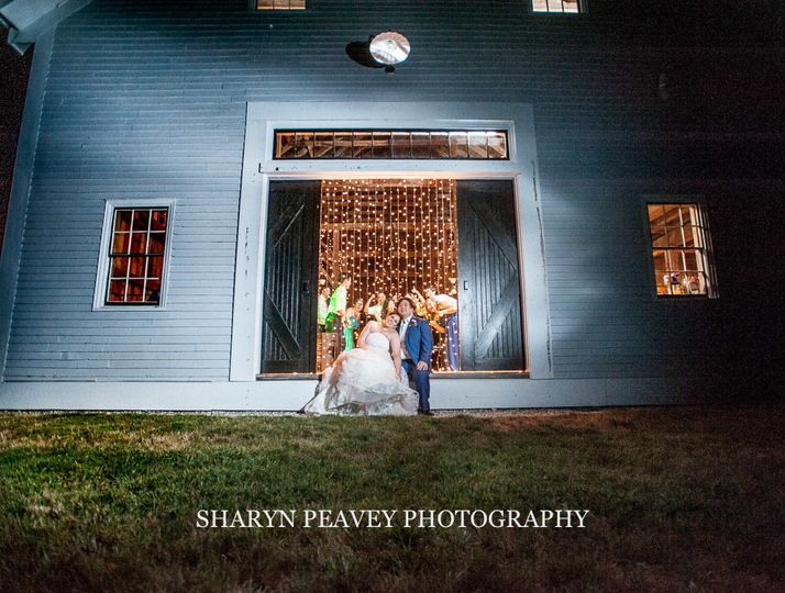 Bride and groom taking time for portraits at Flanagan Farm in front of Event Light Pros lighting.