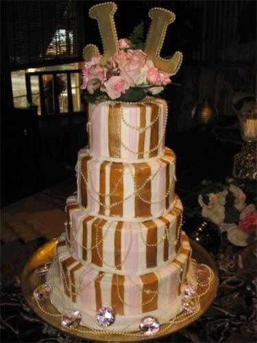 With the gold stripes, draped pearls, and big jewels, this cake would be right at home in your...