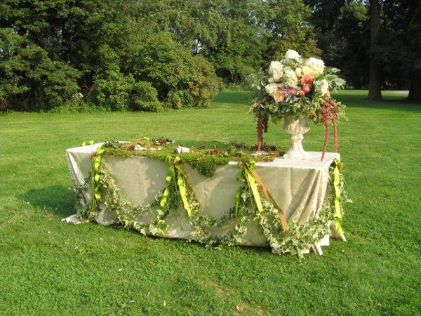 Le Reve Floral Design created the ivy and ribbon swags around the base of the table cloth, and a...