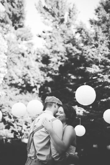 First moments of joy as husband and wife on the dance floor at a beautiful outdoor July wedding in...