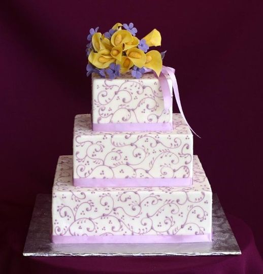 Fondant cake covered with lilac swirl pattern, topped with edible sugar flowers