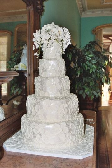 A stunning brocade wedding cake decorated with fully opened sugar roses, hydrangea, orchids, and...