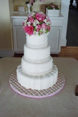 A gorgeous rolled fondant wedding cake decorated with hand made sugar peonies and hydrangeas.