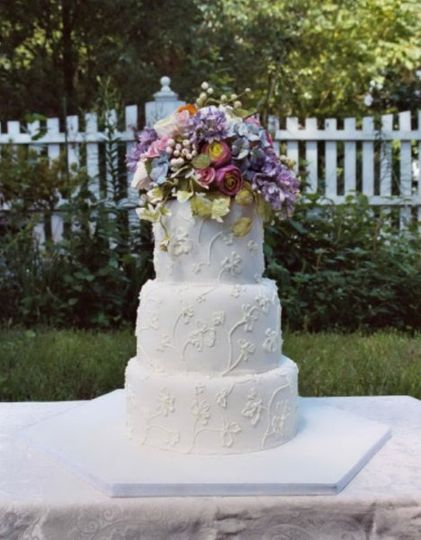 A gorgeous summer wedding cake decorated with hand painted brush embroidery.  Lilac, ranunculus,...