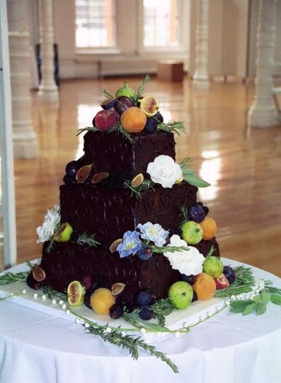 A rich cake covered in imported chocolate with sugar flowers, fresh figs, apricots, rosemary & sage....