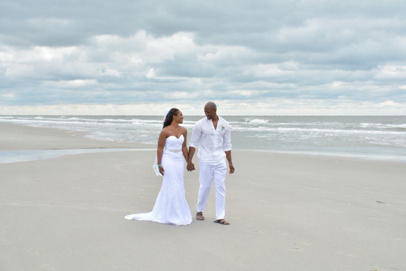 Newlyweds walking along the beach