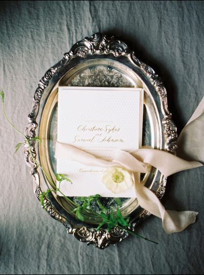 Invite with gold ribbon on a plate
