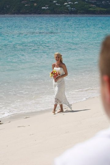 Bride walking along the shore