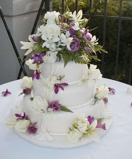 Three tier wedding cake with purple and white flowers