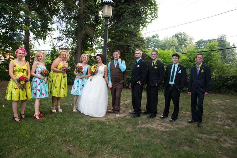 Here is the complete bridal party with the brides maids in colorful cotton print dresses and the...