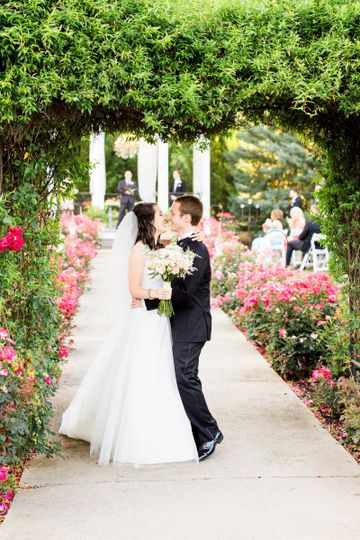 Newlyweds kissing under the arch