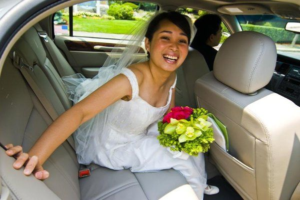 Waiting to come in for her wedding the bride sits in the car with her flowers. Boston, MA