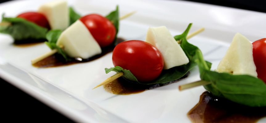Caprese Skewers: fresh mozzarella, grape tomatoes, and basil atop a honey balsamic glaze.
