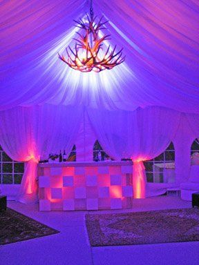 Backlighting of custom fabric treatment in a tent and uplighting of tent legs