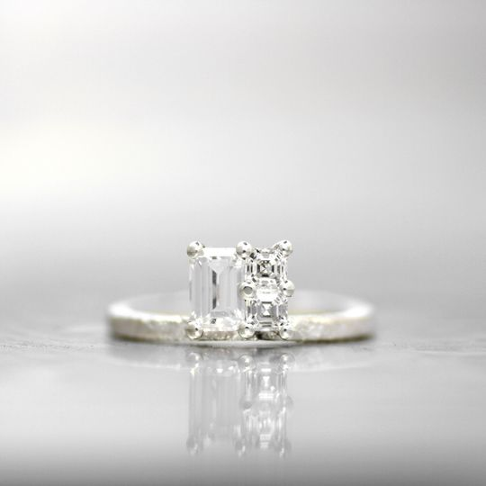 GENEVAThis simple offset cluster gives the allure of a single large square diamond in this stunning...