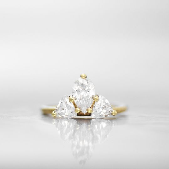 VERSAILLESA unique combination of diamond shapes in a clustered prong setting, this engagement ring...