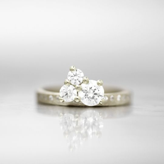 MADIERA  This simple offset cluster gives the allure of a single large triangular diamond in this...