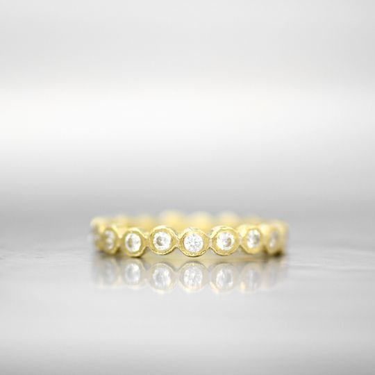 ATHENS  This eternity band adds shape and elegance with a soft row of diamond bezels. The signature...