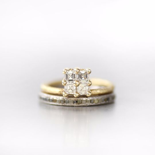 Yellow gold engagement ring with four stacked asscher cut diamonds, paired with a white gold rough...