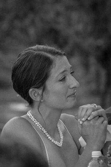Bride sheds a tear during emotional wedding toast.