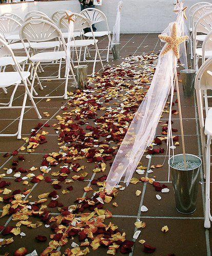 A rose petal carpeted aisle with Sea Stars and tullle