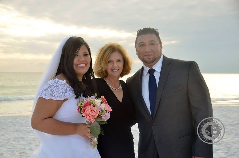 Newlyweds and the officiant at the beach