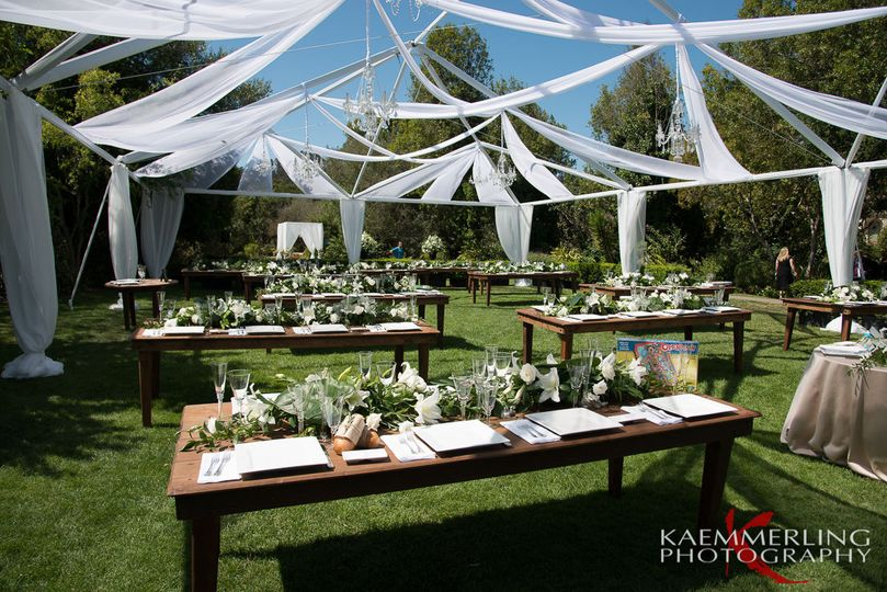Outdoor wedding reception with farm tables and chandeliers