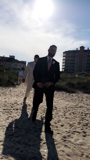 Groom and officiant walking to the venue