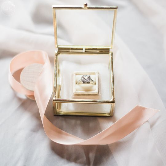 Beautiful gold rimmed glass box detail shot of the ring. With peach/pink ribbon to accent the...