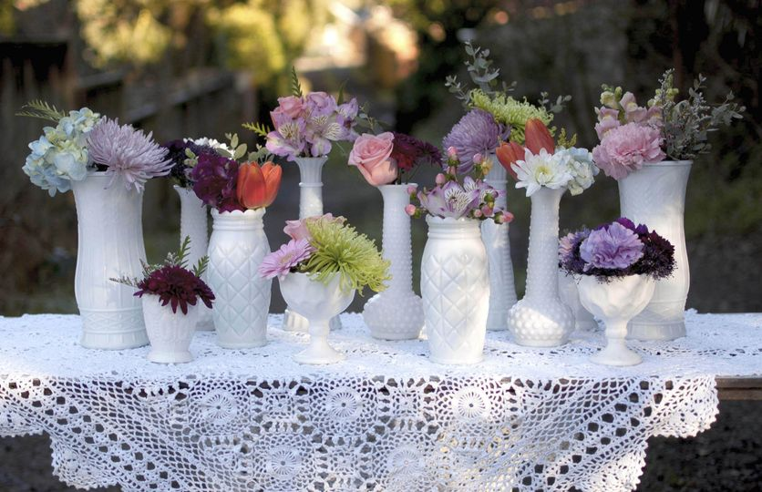Pictured here is our collection of antique-inspired heirloom milk glass vases. Add one of our lace...