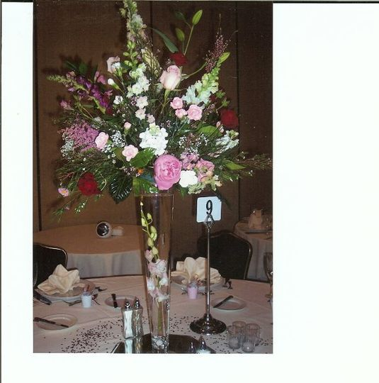 "Centerpiece of white and pink flowers resting on 24"" pilsner vase with floating dendrobium orchid...."