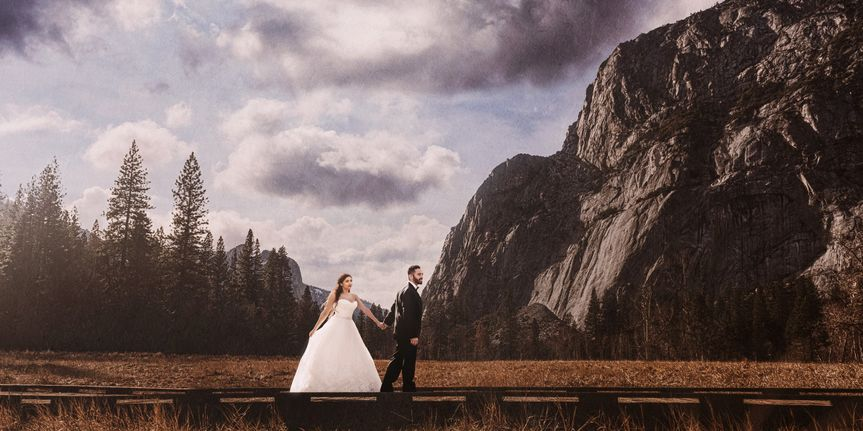 Photograph of the bride and groom walking along a wooden path, hand-in-hand, in Yosemite Valley,...