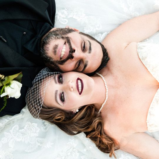 Photograph of the bride and groom laying down on the ground on top of the bride's dress for a...