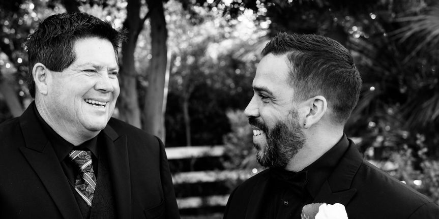 Black and white photograph of the groom sharing a laugh with the father of the bride before the...