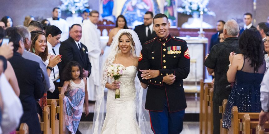 Photograph of the beautiful bride and her handsome marine groom walking down the aisle after just...