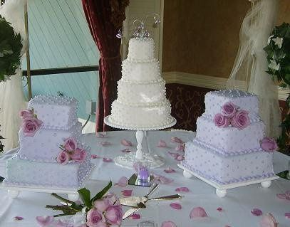 Trio of miniature wedding cakes displayed on beautiful pedestals.