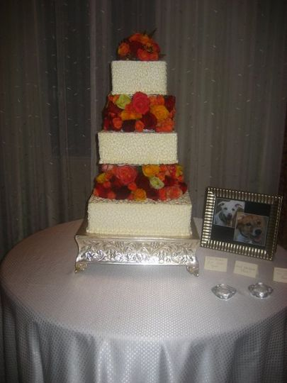 Fall flowers,is a squared three tiered cake with a lace design and fresh flowers.