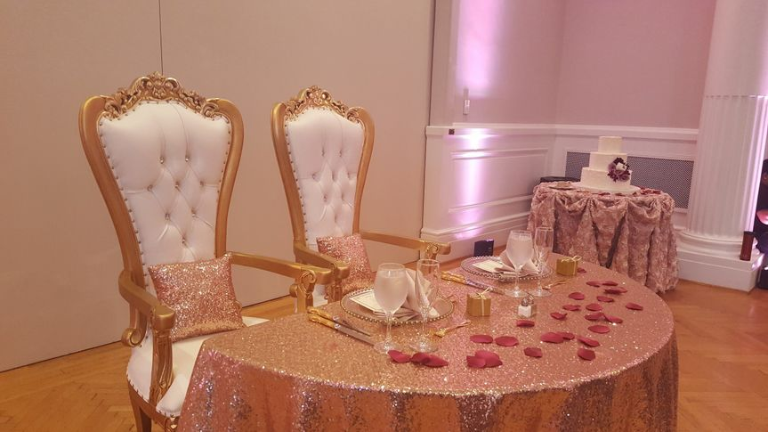 Understated head table featuring sparkly gold and red flower petals