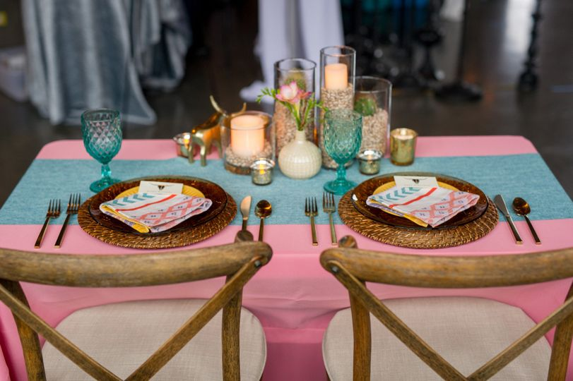 Casual, southwest inspired sweetheart table complete with cacti and a gold bull.   Photo by Aralani...
