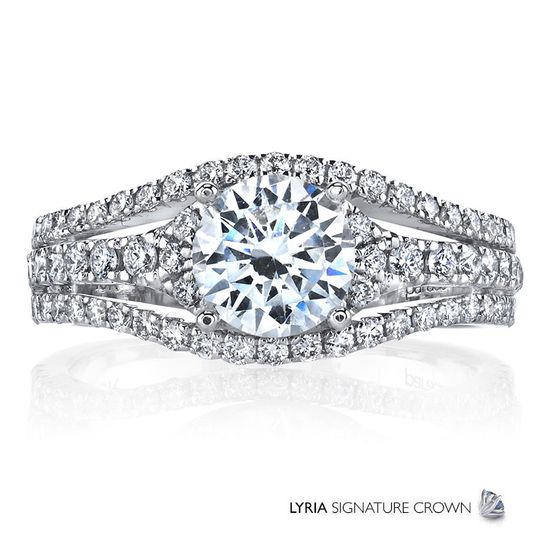 Three split rows of sparkling white diamonds present a brilliant center stone in this contemporary...