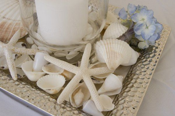 Seashells,starfish & hydrangea blooms nestled on a silver tray with hurricane glass and flickering...