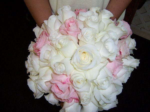 Open white roses accented with pink roses with a collar of foliage