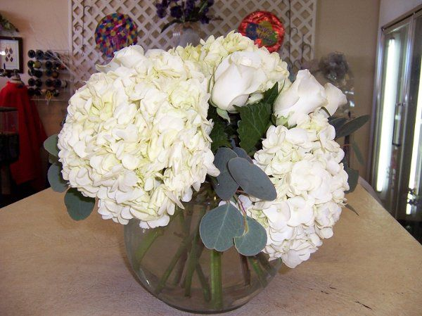 Bubble bowl filled to capacity with white hydangea,white roses and accent foliage of silver dollar...