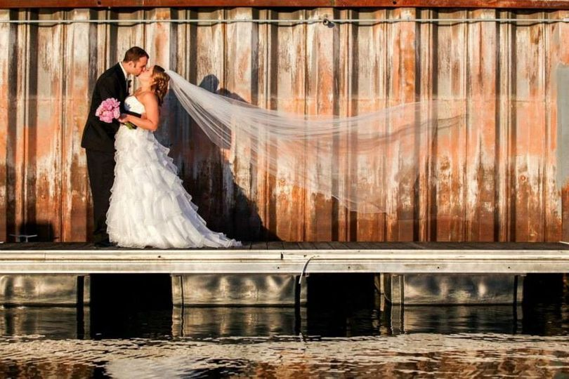 Newlyweds kiss by the water