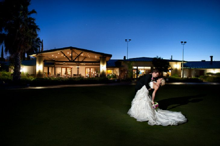 Bride and Groom near patio of the Antelope Valley Country Club at night.