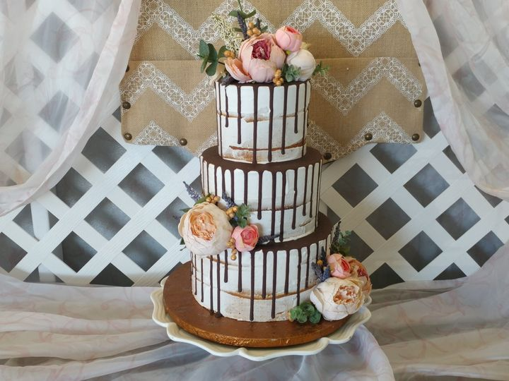The naked cake, dripping in ganache, finished with fresh florals.